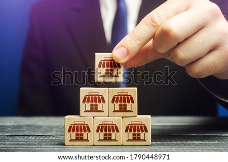 A man builds a pyramid from blocks of business shops. Building a successful business empire. Expansion and competitive growth. Franchise concession concept. Commercial network development. Сток-фото ©