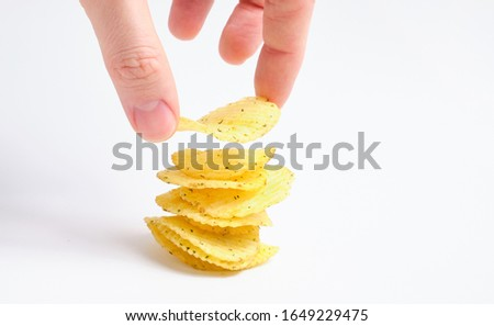 A man builds a stack of chips with his hand. The concept of delicious perfect cooked. Close up.