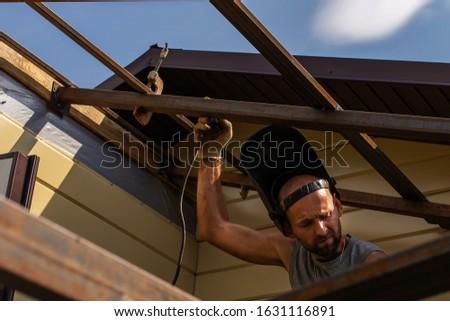 A man builds a wooden house, a welder