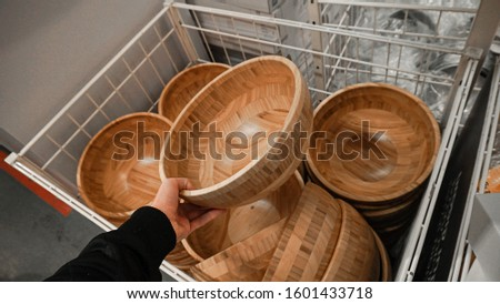 A man buys wooden dishes in a shop