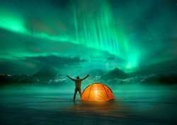 A man camping in wild northern mountains with an illuminated tent viewing a spectacular green northern lights aurora display. Photo composition.