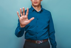 a man can be seen half-face shows the 5 fingers hand on a gray background
