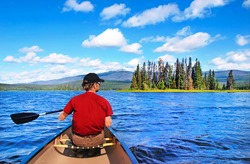 A man canoeing on a lake in the wilderness of British Columbia, Canada