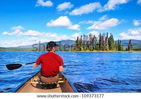 a man canoeing on a lake in the ...