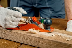 A man carpenter engaged in woodworking planes the surface of a wooden Board in his workshop with a hand plane. Concept of repair and construction.