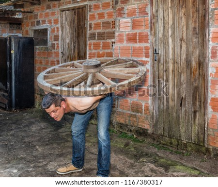 A man carries a wooden wheel on his back. #1167380317