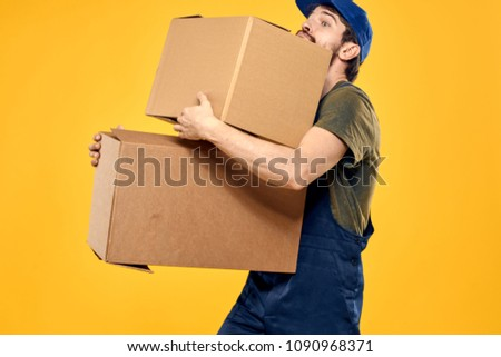 a man carries heavy boxes                             #1090968371