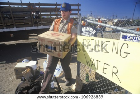 A man carrying drinking water away from a relief station in Santa Clara after the 1994 earthquake