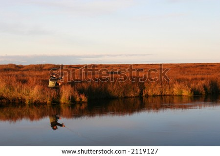 A man casting a fly in a calm river in autumn