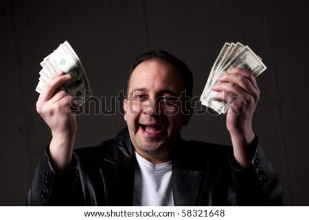 A man celebrating holding handfuls of green American cash money. Shallow depth of field with focus on the face.