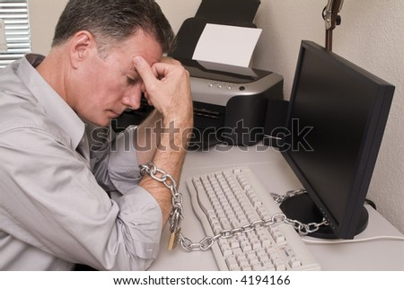 A man chained to his computer with an expression of fatigue or intense boredom.