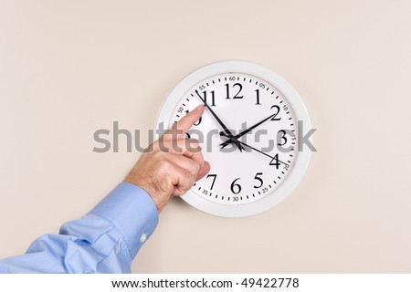 A man changes the time on a clock, moving it forward in time, spring forward.
