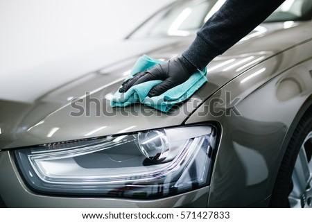 A man cleaning car with microfiber cloth, car detailing (or valeting) concept. Selective focus. #571427833