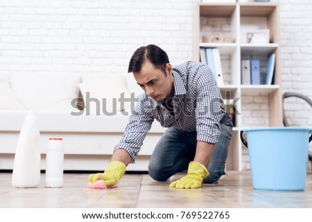 A man cleaning the floor in the apartment. Handyman is cleaning the apartment. #769522765