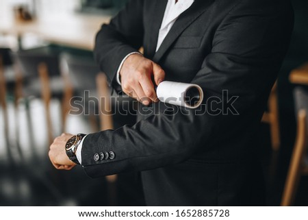 a man cleans a black jacket with a roller