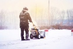 A man cleans snow from sidewalks with snowblower.