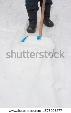 A man cleans the sidewalk from snow by the blue shovel on a winter day. #1578003277