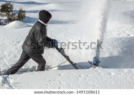 A man clears a path with a snow blower on a clear winter frosty sunny day. #1491108611