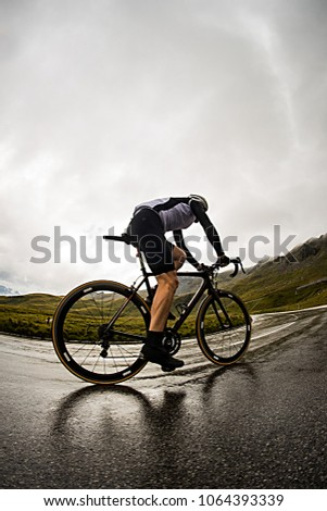 A man climbing on a hill with his bicycle in a rainy and slippery condition on a curve on the road to Grossglockner in Austria. Storm approaching towards the cyclist.