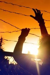 A man climbs over the fence.