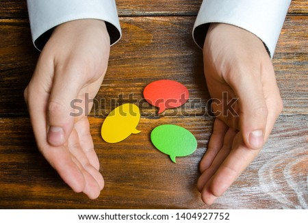 A man collects multicolored speech bubbles in his hands. Listen to other opinions and points of view, accepting criticism and comments. Reverse contact with customers and buyers. Freedom of speech.