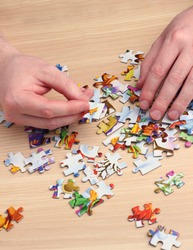 A man collects puzzles with his hands on a wooden table. Children's games.