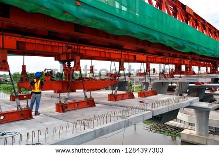 A Man controls the box girder to build a bridge. segmental bridge box girders ready for construction.segments of long span bridge box girder.in stall box girder.construction site.