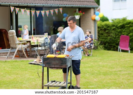 A man cooking meat on barbecue for summer family dinner at the backyard of the house