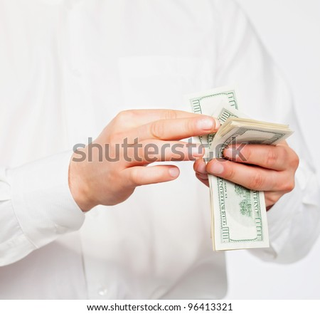 A man counting a handful of dollars.