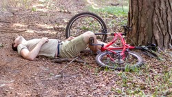 A man crashed into a tree while cycling in forest and lost consciousness. An accident while cycling. Insurance concept.