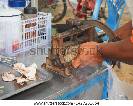 A man crushing dried squids with old machine (only hand in picture), local Thai snacks and street food.