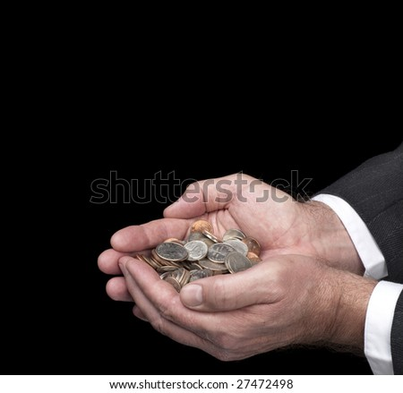 A man cups his hands as he holds a pile of coins.  Image was shot against a black backdrop and is not a cutout.