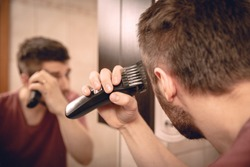 A man cuts his hair on his head with an electric razor