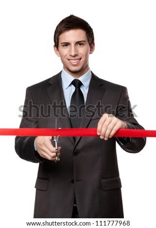 A man cutting a red ribbon with scissors, isolated on white