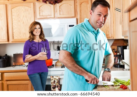 A man cutting vegetables preparing dinner with his wife watching in the background