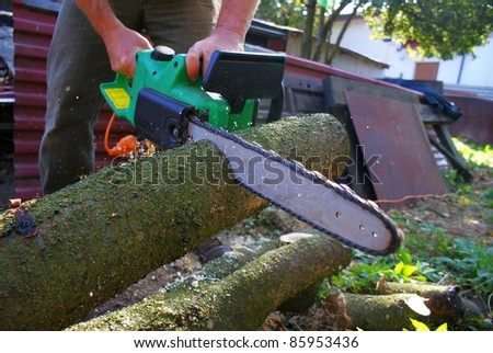 A man cutting wood with mechanical saw