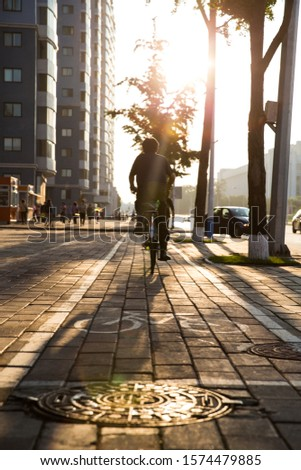 A man cycles home after a day of work, cycling towards the sunset in the wide streets on Pyongyang