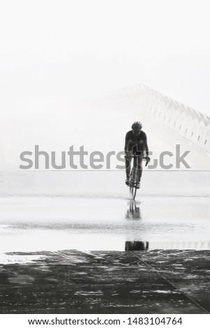 A man cycling during rainy day with perseverance and courage