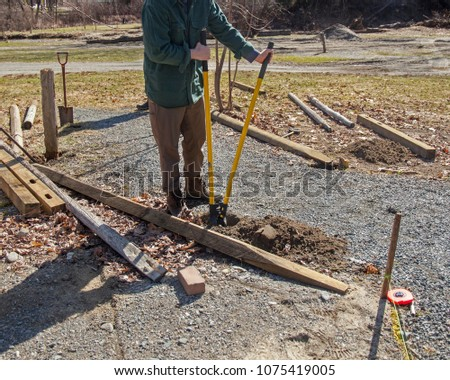 A man digging a hole in the dirt for a fence post at a community park.