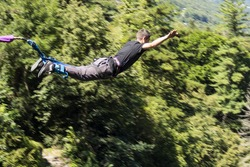 a man doing bungee jumping with a forest in background, extreme sports