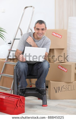 a man doing computer in a room full of cardboards