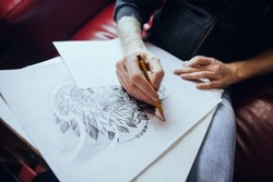 A man draws a picture on a white sheet of paper