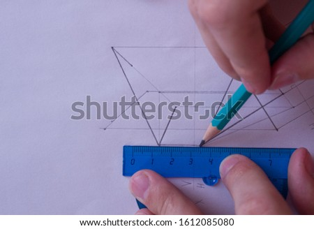 A man draws a scheme on white paper with a pencil using a ruler. Drawing project in pencil on a large sheet of close-up.