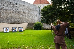 A man dressed as a medieval Archer shoots arrows at targets in a Park