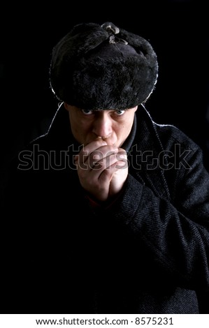 A man, dressed as a Russian, warming his hands
