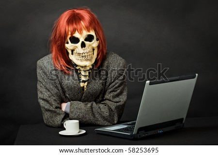 A man dressed as death sits at a table with a computer