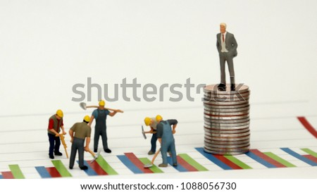 A man dressed in a suit standing on top of a pile of coins against a graph and miniature workers at a construction site below it.