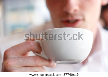 A man drinking coffee in a cafe