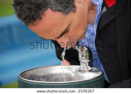 A man drinking water from a water fountain in a park
