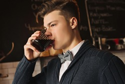 A man drinks in a cafe in a dark vein. A young student in a shirt with a sweater and a bow-tie is spending his leisure time at the bar.
